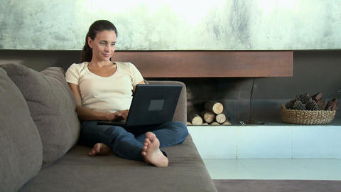 Woman on sofa using laptop computer Stock Video Footage