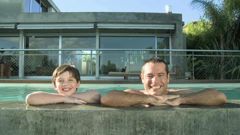 Father and son in swimming pool, smiling at camera Stock Video Footage