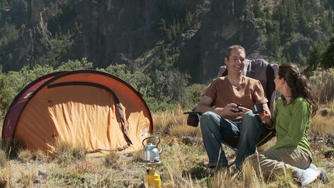 Tilt down from landscape to couple camping Stock Video Footage