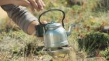 Zoom out from mann pouring drink from kettle to people camping Footage