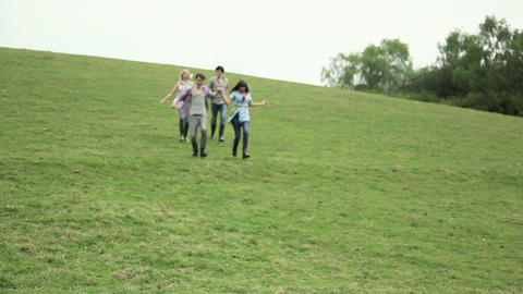 Friends running down a hill Stock Video Footage