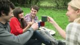 Friends in a field, toasting with mugs and drinking Footage