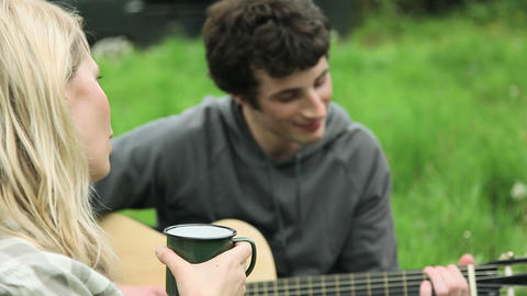 Young woman singing and young man playing guitar for friends outdoors Footage