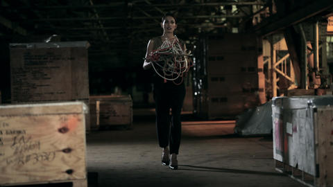 Businesswoman walking through warehouse, carrying cables Stock Video Footage
