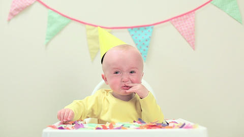 Baby boy sitting in highchair with bunting Stock Video Footage