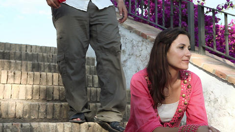 Young couple sitting on steps, man giving woman flower Stock Video Footage