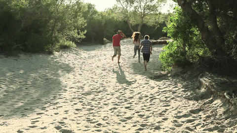 Three young friends running on sand Footage