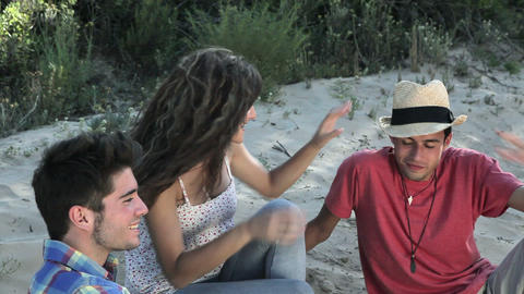 Three young friends sitting on beach Stock Video Footage