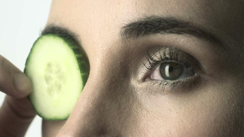Young woman placing cucumber slice over her eye Stock Video Footage