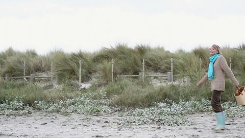 Woman walking along beach Stock Video Footage