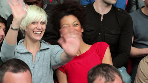 Spectators in crowd talking, young women pointing and waving Stock Video Footage