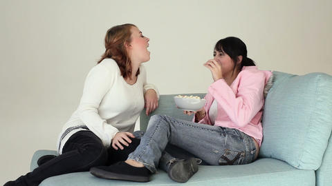 Teenage girls throwing popcorn to each other Stock Video Footage