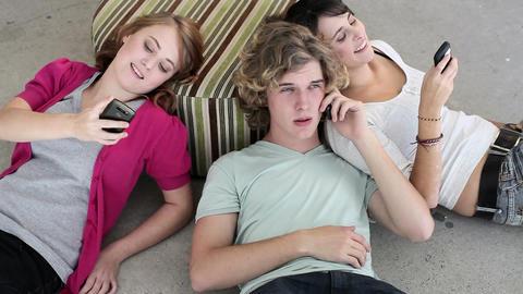 Three teenagers lying on floor looking at smartphones Stock Video Footage