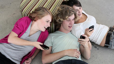 Three teenagers lying on floor looking at smartphones Stock Video Footage
