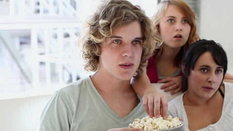 Three teenagers watching TV and eating popcorn Stock Video Footage