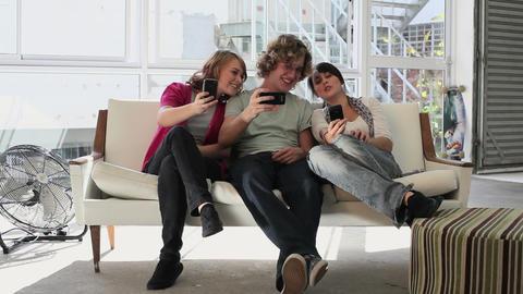 Three teenage friends looking at smartphones Stock Video Footage