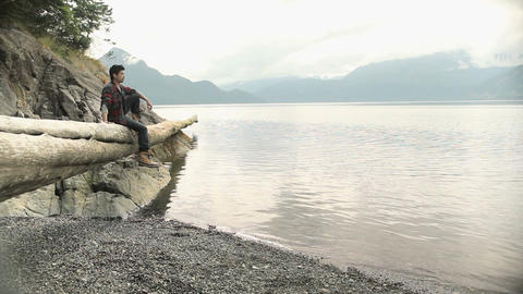 Young man sitting on log by lake Stock Video Footage