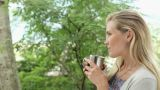 Mid adult woman drinking hot drink Footage