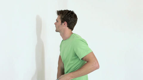 Man hammering nail into wall and woman hanging picture Stock Video Footage
