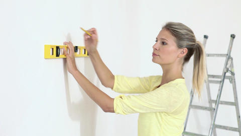 Young woman using spirit level on wall Stock Video Footage