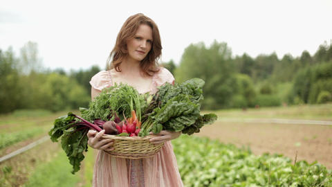 Woman on farm with basket of fresh vegetables Stock Video Footage