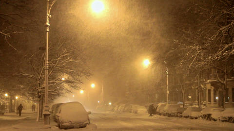 Night time view of a street in the snow, illuminated by street lights Footage