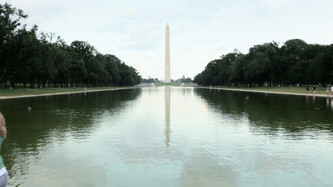 Young woman walking by reflecting pool and the washington... Stock Video Footage