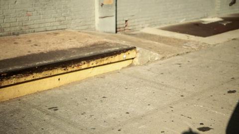 Skateboarder doing trick on sidewalk Stock Video Footage