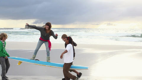 Boys carrying girl on beach on surfboard Stock Video Footage