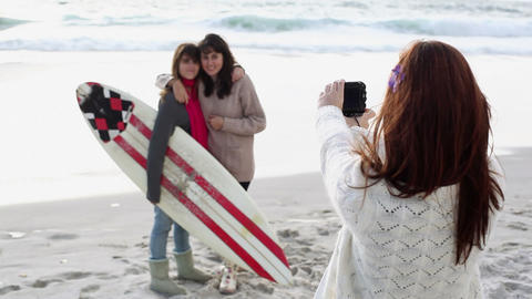 Girl taking photograph of two friends on beach with... Stock Video Footage