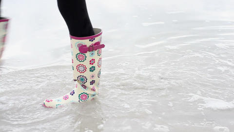 Girl walking in wellington boots paddling in the sea Stock Video Footage
