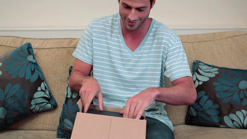 Young man opening parcel containing book Stock Video Footage