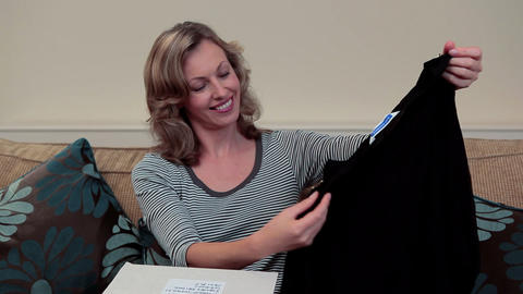 mature woman opening parcel containing clothing Stock Video Footage