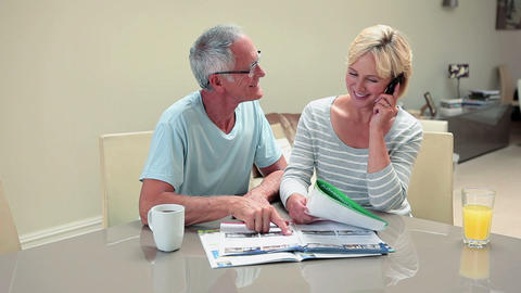 Mature couple looking at magazine, woman on mobile phone Stock Video Footage