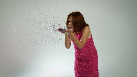 Girl wearing pink dress blowing ticker tape Stock Video Footage