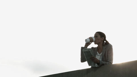 Businesswoman drinking coffee and reading newspaper Stock Video Footage