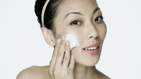 Young woman cleansing her face Stock Video Footage