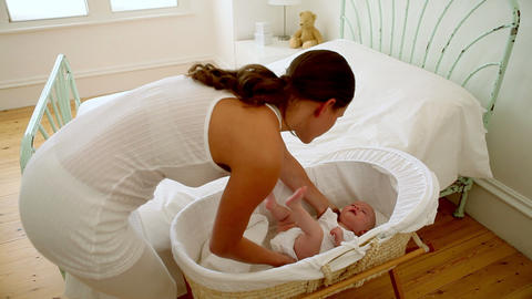 Tired mother putting baby in bassinet and lying on bed Stock Video Footage