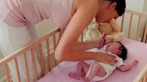 Mother placing baby in crib Stock Video Footage