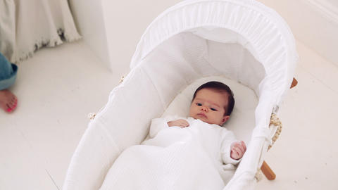 Mother taking baby girl out of bassinet Stock Video Footage