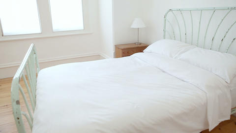 Bed in minimally decorated room Stock Video Footage