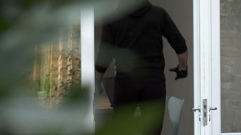 Burglar breaking into house and stealing laptop Stock Video Footage