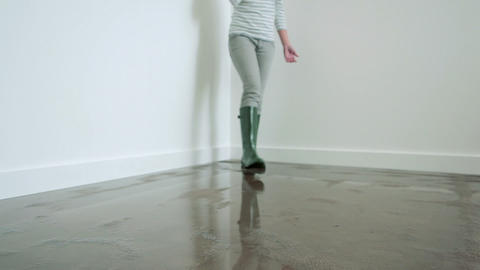 Young woman standing on flooded floor on phone Stock Video Footage