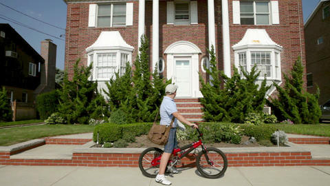 Newspaper boy on bike throwing newspaper into front yard Stock Video Footage