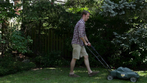 Man mowing grass with lawnmower Stock Video Footage