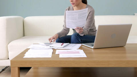 Young woman with paperwork and laptop Stock Video Footage