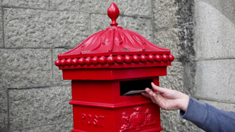 Person putting postcard in post box, London Stock Video Footage