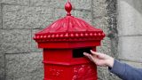 Person putting postcard in post box, London Footage