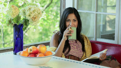 Young woman reading and drinking hot drink Stock Video Footage