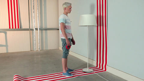 Young man sticking red tape to lampshade Stock Video Footage